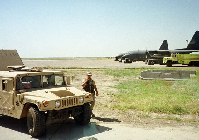 US Army soldier walks past a Humvee at the Karshi-Khanabad air base in Uzbekistan, 28 May 2002