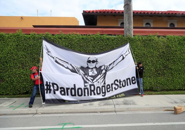 Demonstrators display a banner calling for the pardoning of former Trump presidential campaign advisor Roger Stone, as the presidential motorcade passes through West Palm Beach, Florida