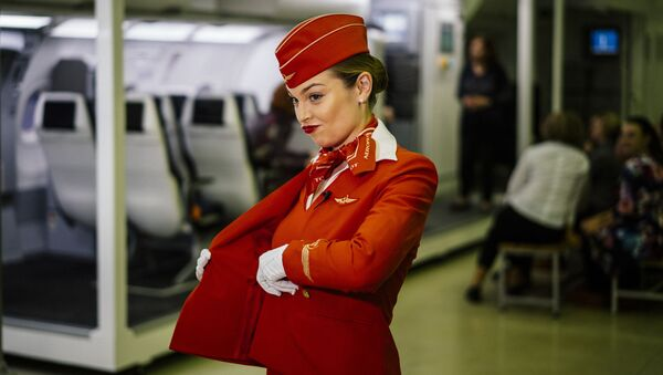A stewardess puts on her jacket as flight staffers practise emergency landing techniques at the Russian Aeroflot company Training Complex of the Aviation Personnel Training Center for search-and-rescue training LAND-WATER at Sheremetevo airport outside Moscow on December 25, 2019 - Sputnik International