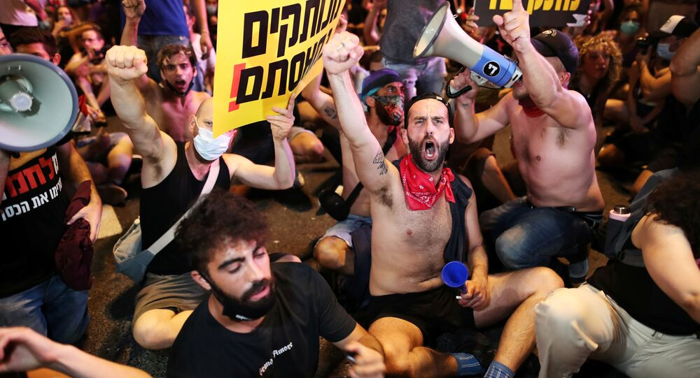 Israelis block a main junction in the city as they protest against the government's response to the financial fallout of the coronavirus disease (COVID- 19) crisis in Tel Aviv, Israel July 11, 2020.