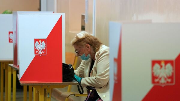 A voter sits behind a voting booth on July 12, 2020 in Warsaw during the second round of Poland's presidential election. - Poles began voting on on July 12, 2020 in a knife-edge presidential election between a populist incumbent closely allied with the US President and a europhile liberal who wants to restore ties with Brussels.  - Sputnik International
