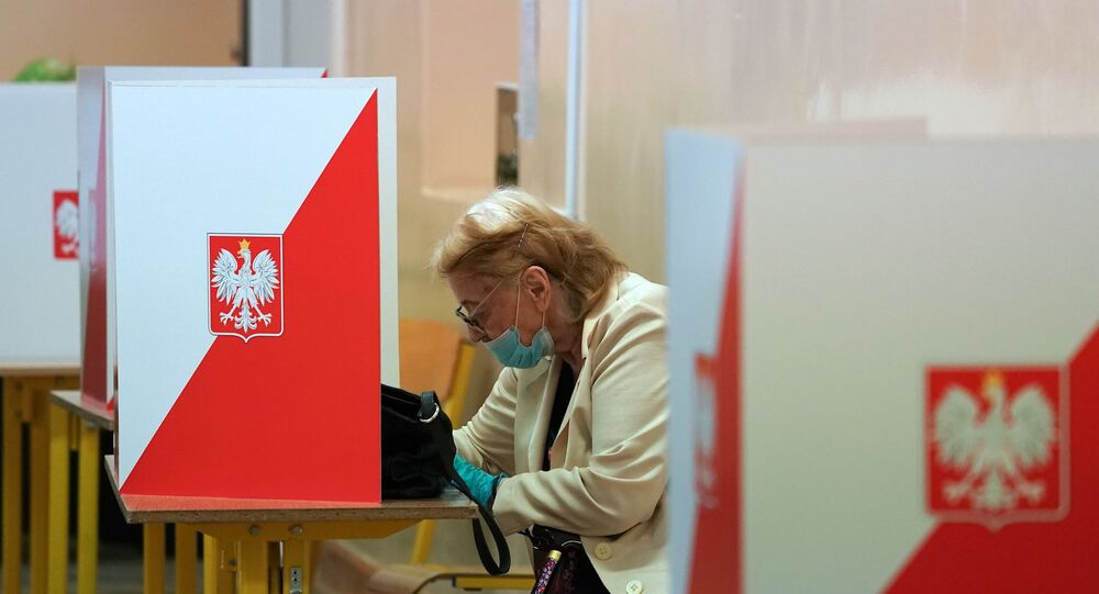 A voter sits behind a voting booth on July 12, 2020 in Warsaw during the second round of Poland's presidential election. - Poles began voting on on July 12, 2020 in a knife-edge presidential election between a populist incumbent closely allied with the US President and a europhile liberal who wants to restore ties with Brussels.