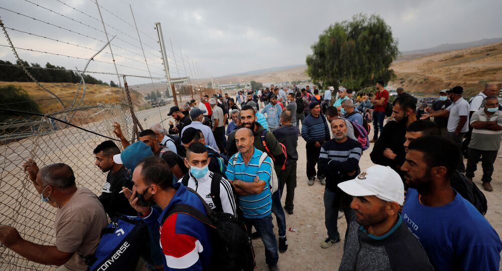 Palestinian labourers, who were not able to cross into Israel for work, gather near an Israeli checkpoint that was closed amid fears of a second wave of coronavirus disease (COVID-19) infections, near Hebron in the Israeli-occupied West Bank 29 June 2020.