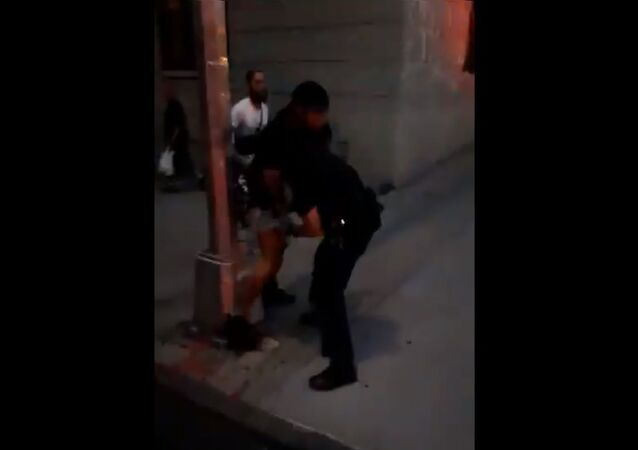 An unidentified protester gets NYPD police officer in a headlock