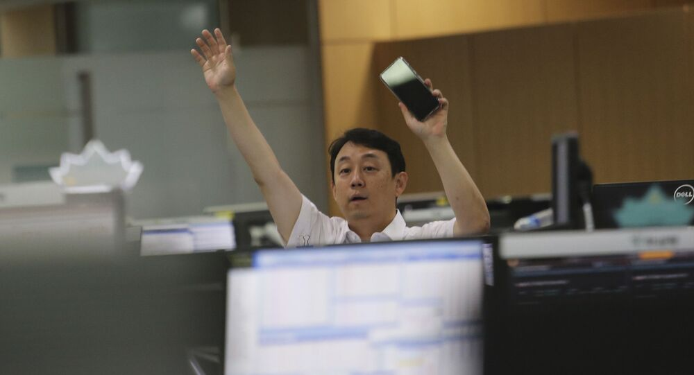 A currency trader gestures at the foreign exchange dealing room of the KEB Hana Bank headquarters in Seoul, South Korea, Thursday, July 9, 2020.