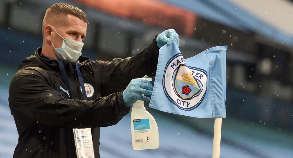 A member of the ground staff spray the corner flag during the English Premier League football match between Manchester City and Arsenal at the Etihad Stadium in Manchester, north west England, on June 17, 2020