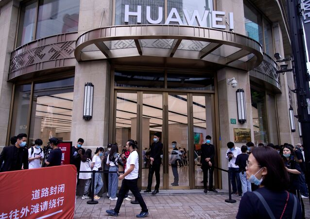 People stand in line in front of Huawei's new flagship store, as it officially opens in Shanghai, following the coronavirus disease (COVID-19) outbreak, China, June 24, 2020