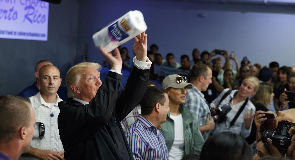 In this Tuesday, Oct. 3, 2017 photo, President Donald Trump tosses paper towels into a crowd at Calvary Chapel in Guaynabo, Puerto Rico
