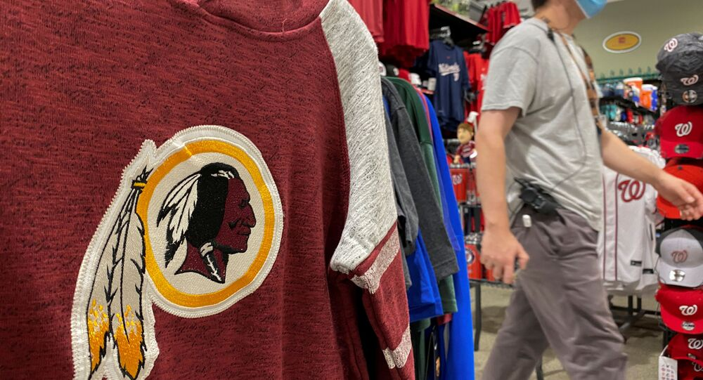 An employee passes a Washington Redskins football shirt for sale at a sporting goods store in Bailey's Crossroads, Virginia, US, 24 June 2020.