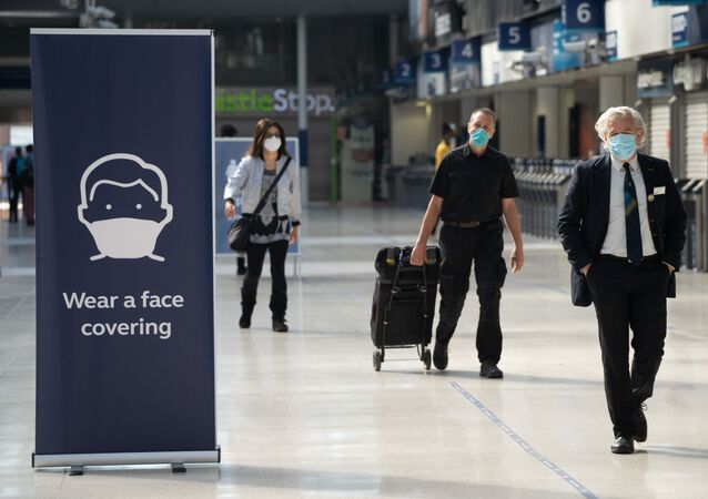 Commuters wearing face masks walk through the concourse at Waterloo Station in London on 15 June 2020 after new rules make wearing face coverings on public transport compulsory while the UK further eases its coronavirus lockdown.