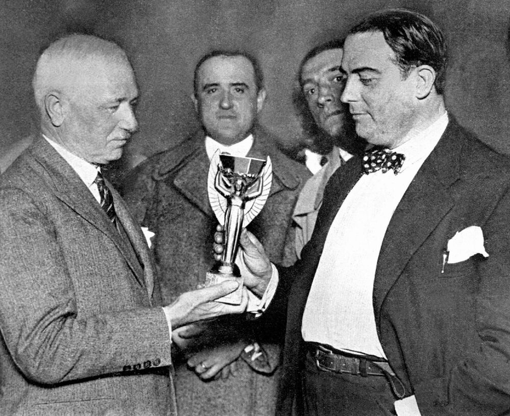 Frenchman Jules Rimet (left), head of the International Federation of Association Football (FIFA) presents the World Cup trophy to Dr. Raul Jude, president of the Uruguayan Football Association on 5 July 1930 in Montevideo. The trophy will be presented to the captain of the winner team of the first World Cup, organised in Uruguay on 13-30 July.