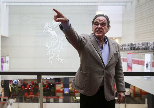 In this photo provided by Tasnim News Agency, American movie director Oliver Stone points in a photo opportunity while attending the Fajr International Film Festival, in Tehran, Iran, Monday, April 23, 2018