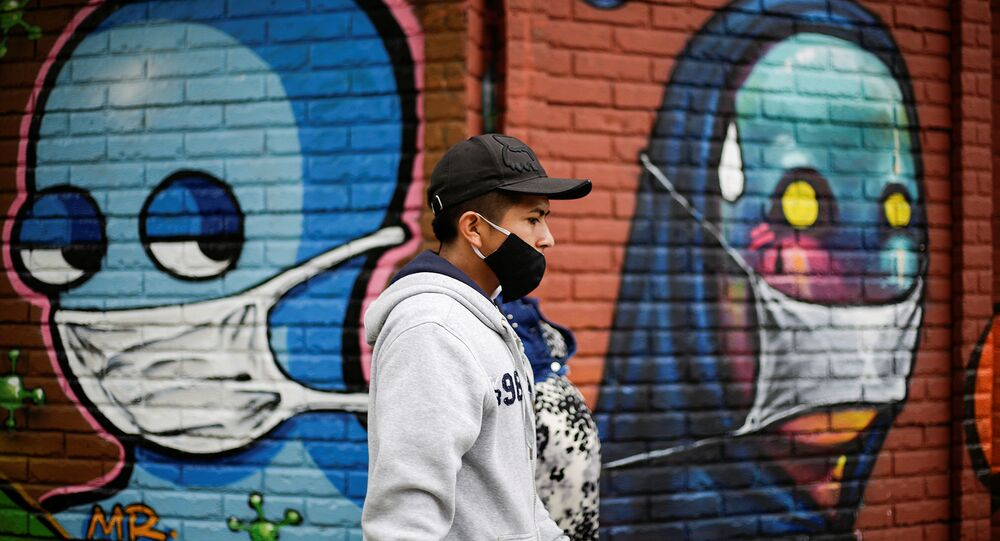A couple wearing face masks walk by a wall with graffitis after health authorities reverse the measures of reopening following the increase in cases of the coronavirus disease (COVID-19) in San Jose, Costa Rica July 13, 2020.