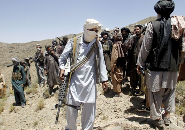 In this Friday, May 27, 2016 photo, members of a breakaway faction of the Taliban fighters walks during a gathering, in Shindand district of Herat province, Afghanistan