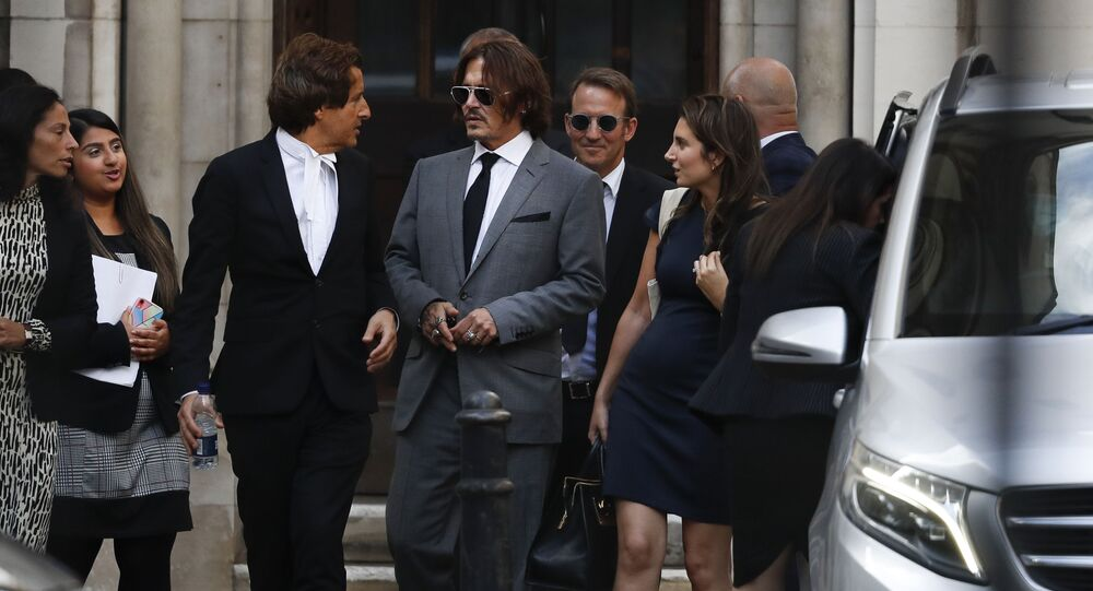 Actor Johnny Depp, centre, leaves the High Court in London, Monday, 13 July 2020