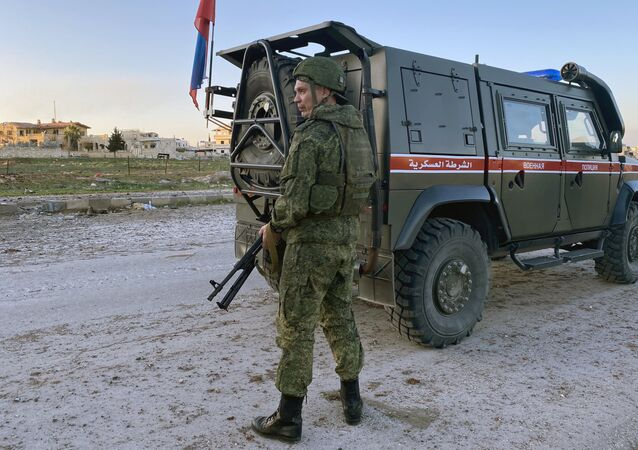 A serviceman of the Russian military police patrols the area near the town of Saraqib, liberated by the Syrian government forces, in Idlib province, Syria