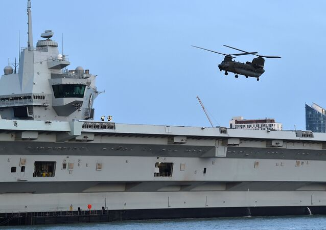 A Chinook helicopter flies over the HMS Queen Elizabeth aircraft carrier, following an event to commemorate the 75th anniversary of the D-Day landings, in Portsmouth, southern England, on June 5, 2019.