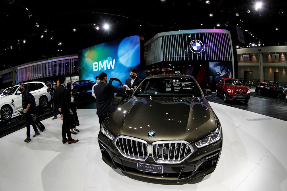 People wearing face masks are seen near the BMW X6 xDrive30d M Sport during the media day of the 41st Bangkok International Motor Show after the Thai government eased measures to prevent the spread of the coronavirus disease (COVID-19) in Bangkok, Thailand July 14, 2020.