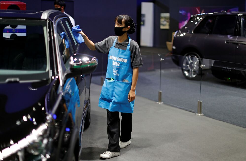 A staff member cleans a vehicle during the media day of the 41st Bangkok International Motor Show after the Thai government eased measures to prevent the spread of the coronavirus disease (COVID-19) in Bangkok, Thailand July 14, 2020.
