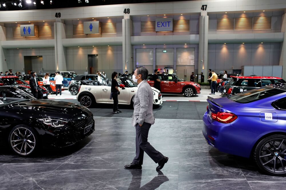 A man wearing a face mask walks between two BMW vehicles during the media day of the 41st Bangkok International Motor Show after the Thai government eased measures to prevent the spread of the coronavirus disease (COVID-19) in Bangkok, Thailand July 14, 2020.