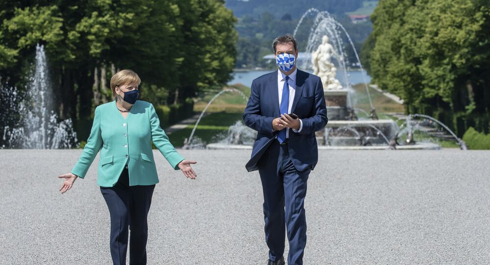 German Chancellor Angela, left, and Markus Soeder, right, Governour of the German state of Bavaria, arrive at the Herrechiemsee island, Germany, Tuesday, July 14, 2020