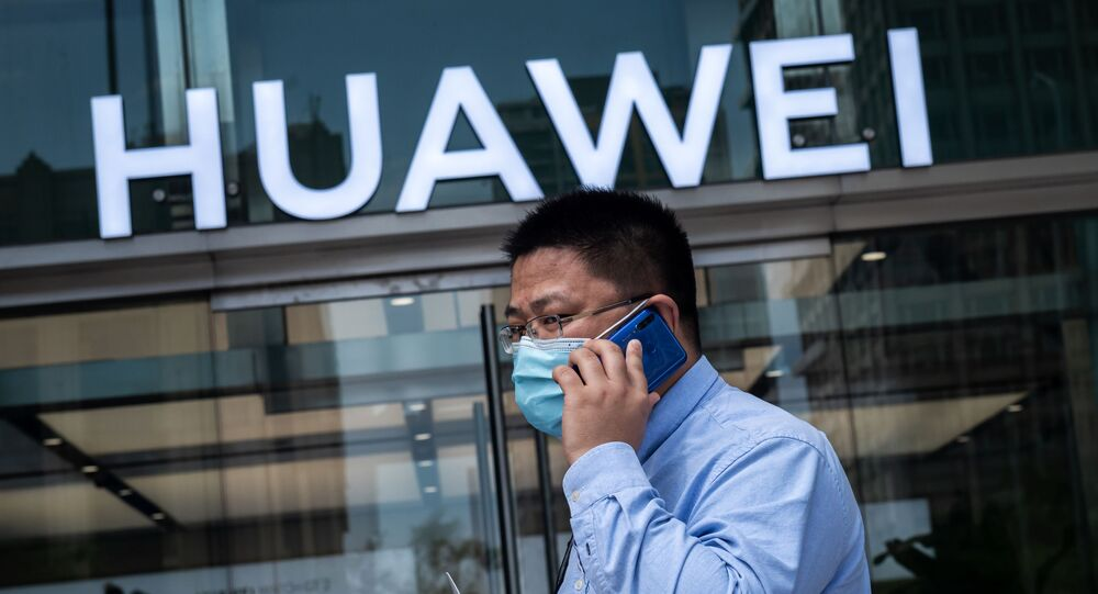 In this file photo taken on May 25, 2020 a man walks past a shop for Chinese telecoms giant Huawei in Beijing, China.