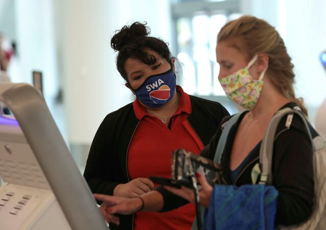A Southwest Airlines Co. employee wears a protective mask while assisting a passenger at Los Angeles International Airport (LAX) in Los Angeles, California, 23 May 2020.