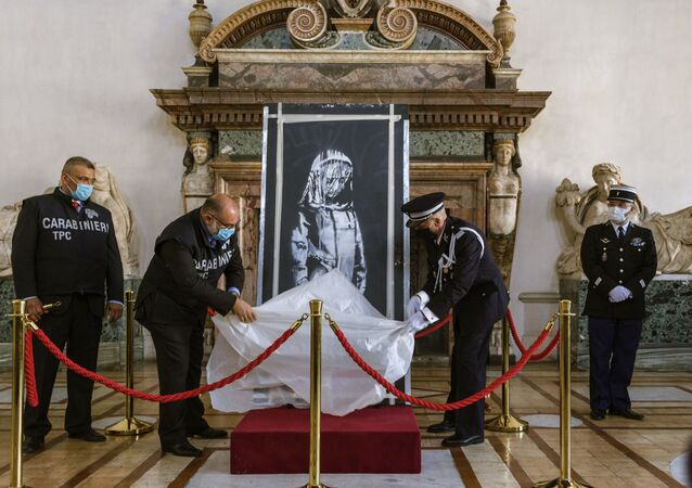 A recovered stolen artwork by British artist Banksy, depicting a young female figure with a mournful expression, that was painted as a tribute to the victims of the 2015 terror attacks at the Bataclan music hall in Paris, is unveiled during a ceremony at the French Embassy in Rome, Tuesday, July 14, 2020, where it was returned by Italian prosecutors to France. The artwork was stolen in 2018 and recovered in June 2020 in Sant'Omero, central Italy by Italian Carabinieri.
