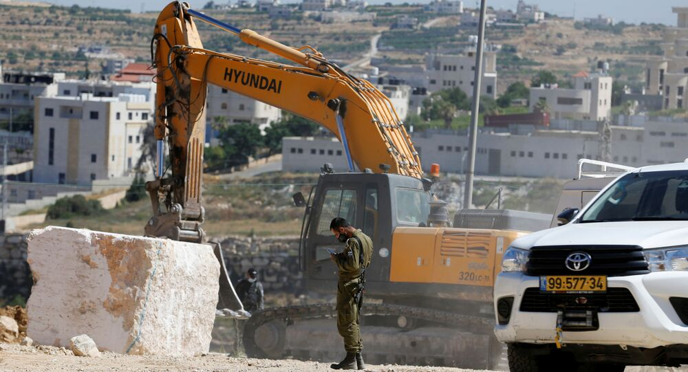A member of Israeli security forces uses a mobile phone as a machinery removes stone blocks placed by Palestinians in Hebron in the Israeli-occupied West Bank July 2, 2020.
