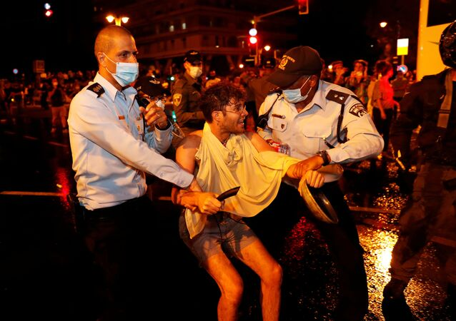 Policemen hold a man during a protest against Israeli Prime Minister Benjamin Netanyahu and his government's response to the financial fallout of the coronavirus disease (COVID-19) crisis outside Prime Minister Benjamin Netanyahu's residence in Jerusalem July 15, 2020.