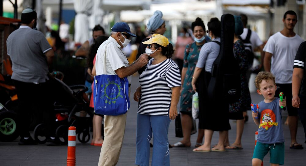 A man fixes a woman's face mask amid the spread of the coronavirus disease (COVID-19), in Ashkelon, Israel, 6 July 2020.