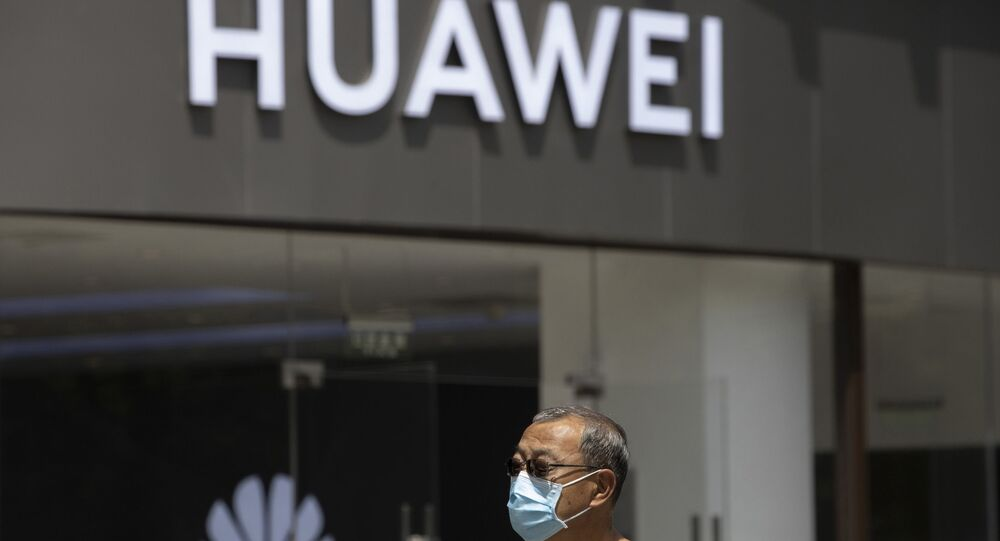 In this 18 May 2020, file photo, a man wearing a face mask to protect himself against coronavirus walks past a Huawei retail store in Beijing