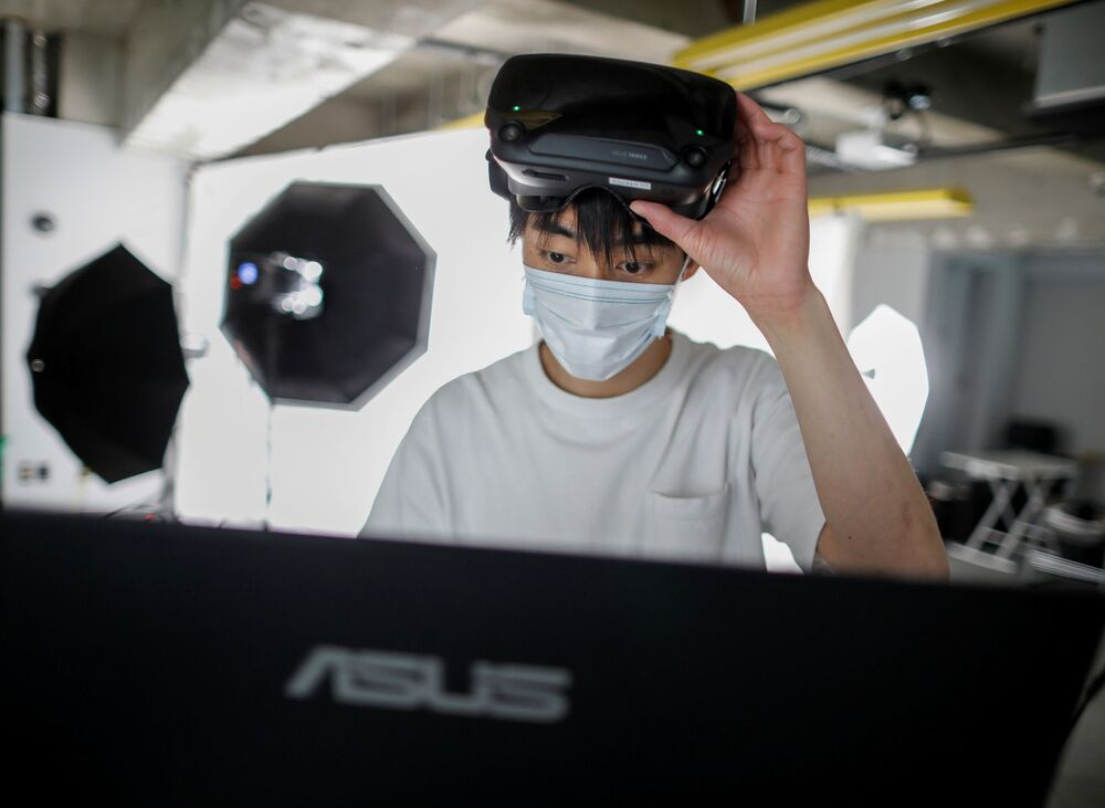 A staff member of Telexistence uses virtual reality technology as he prepares to control the company's shelf-stacking avatar robot, designed to resemble a kangaroo and developed to work in a convenience store, during a photo opportunity ahead of its unveiling in Tokyo, Japan July 3, 2020.