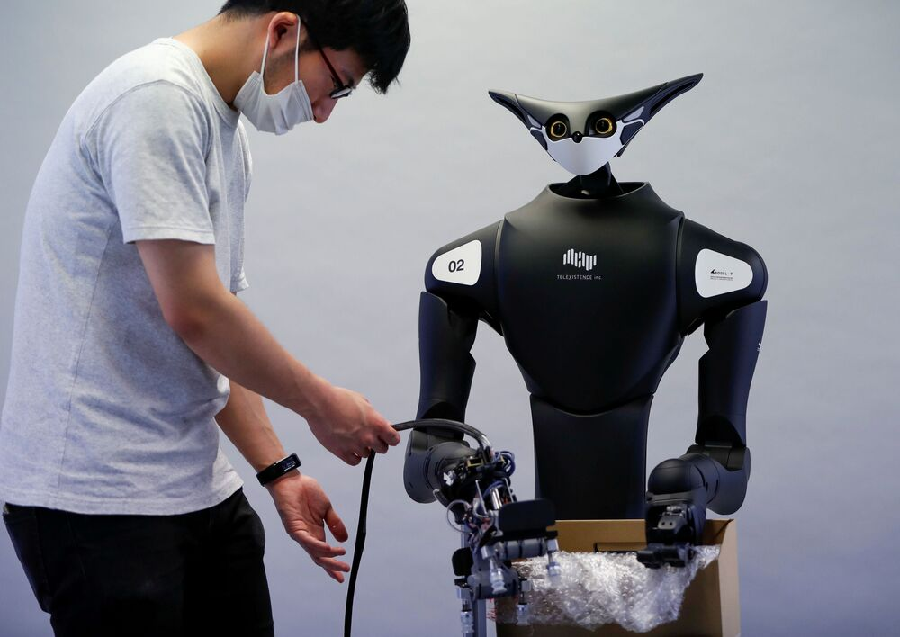 A staff member of Telexistence checks the company's shelf-stacking avatar robot during a photo opportunity ahead of its unveiling in Tokyo, Japan on 3 July 2020.