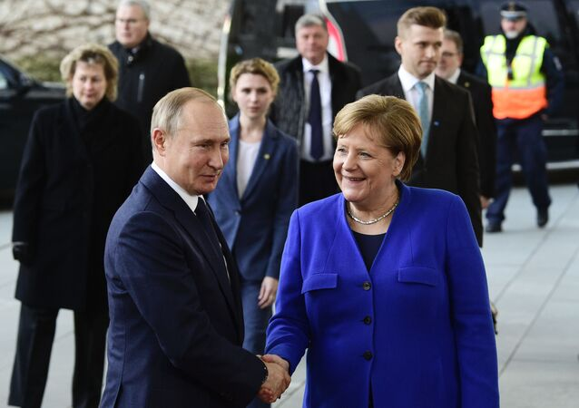 German Chancellor Angela Merkel, right, shakes hands with Russian President Vladimir Putin during arrivals for a conference on Libya at the chancellery in Berlin, Germany, Sunday, Jan. 19, 2020
