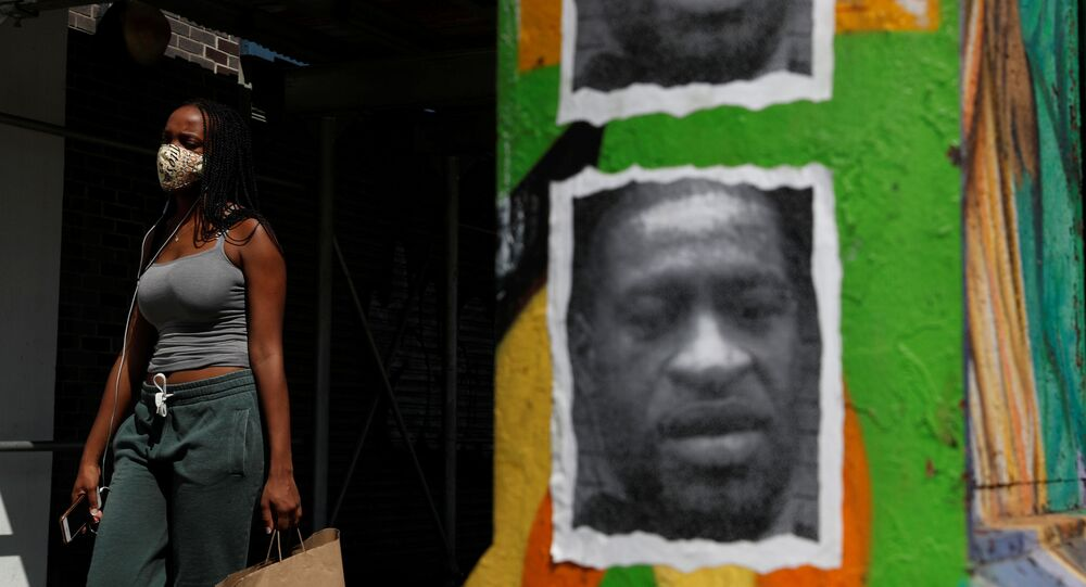 A woman walks with a protective face covering past a mural of George Floyd, in the aftermath of his death in Minneapolis police custody, along 125th street in the Harlem neighborhood of  New York City, New York, U.S., July 9, 2020.