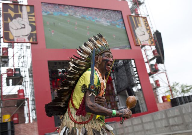 Akazu Tabajara Tapeba dances in front of an outdoors television screen during the group A, 2018 soccer World Cup opening match between Russia and Saudi Arabia, at Praca Maua, in Rio de Janeiro, Brazil, Thursday, June 14, 2018