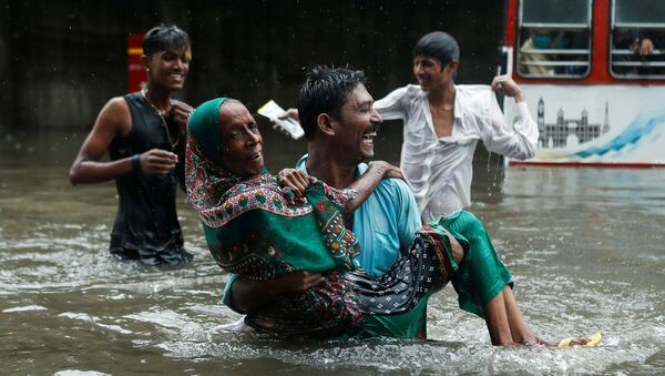 A man carries an elderly woman as they cross a waterlogged street during heavy rainfall in Mumbai, India, July 15, 2020 - Sputnik International