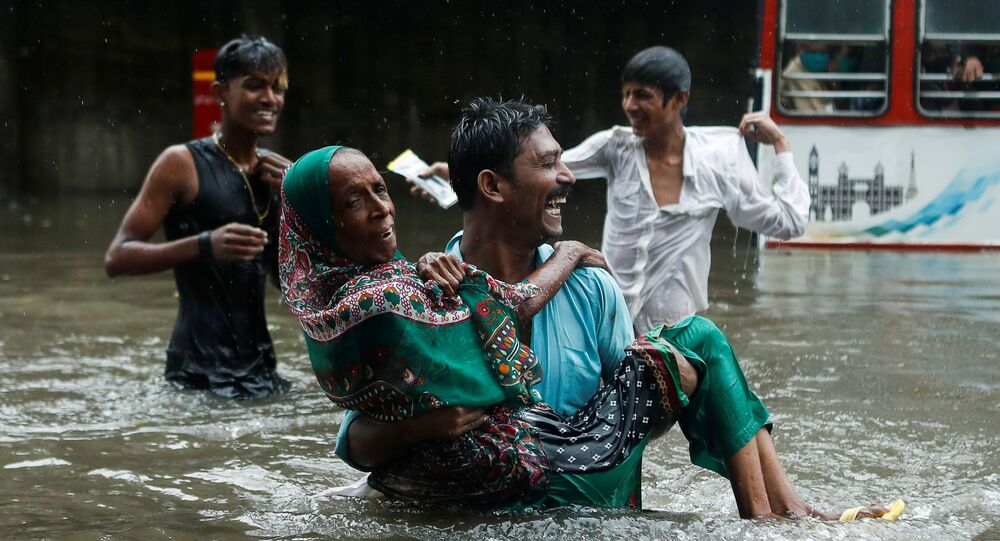 A man carries an elderly woman as they cross a waterlogged street during heavy rainfall in Mumbai, India, July 15, 2020