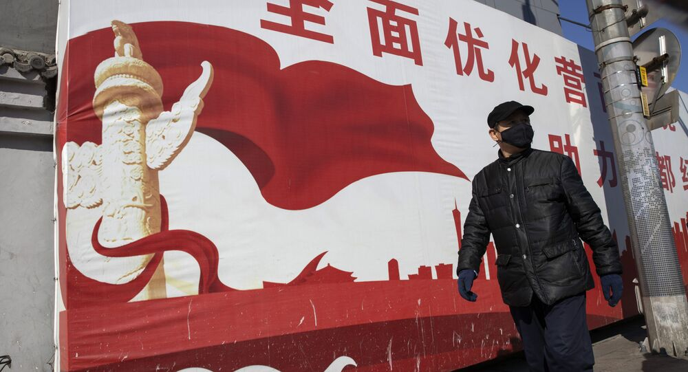 A resident wearing mask walks past government propaganda calling for refinement of the business environment to aid the economic development of the capital in Beijing on Tuesday, March 3, 2020