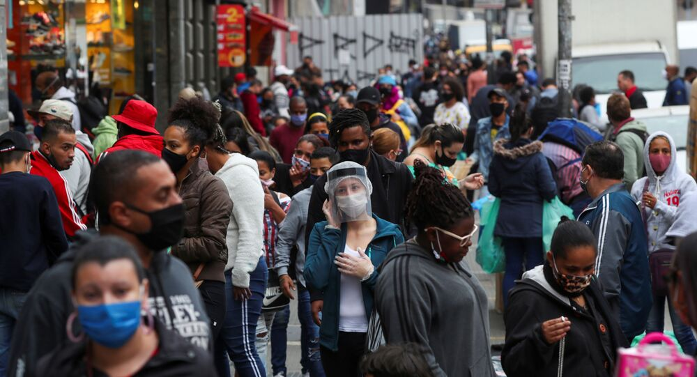 A woman wearing a protective mask and a face shield talks on the phone as people walk at a popular shopping street amid the outbreak of the coronavirus disease (COVID-19), in Sao Paulo, Brazil, July 15, 2020.