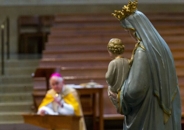 Archbishop Jose H. Gomez of Los Angeles and president of the U.S. Conference of Catholic Bishops (USCCB) kneels in prayer before the Blessed Virgin Mary, in Los Angeles Friday, May 1, 2020