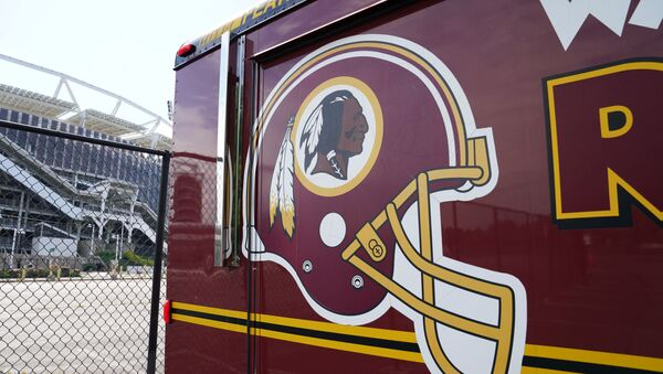 The Washington Redskins team logo is seen on a vehicle parked outside the NFL team's stadium FedEx Field after the team announced it will be abandoning its controversial Redskins team name and logo under pressure from sponsors to scrap the name criticized as racist by Native American rights groups, in Landover, Maryland U.S., July 13, 2020 - Sputnik International