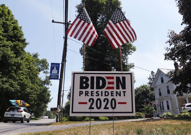 In this 23 June 2020, file photo, a car passes a yard displaying a campaign sign for Democrat presidential candidate, former vice-president Joe Biden in North Hampton, New Hampshire. The coronavirus pandemic isn't going away anytime soon, but campaigns are still forging ahead with in-person organising. The pandemic upended elections this year, forcing campaigns to shift their organising activities almost entirely online and compelling both parties to reconfigure their conventions.