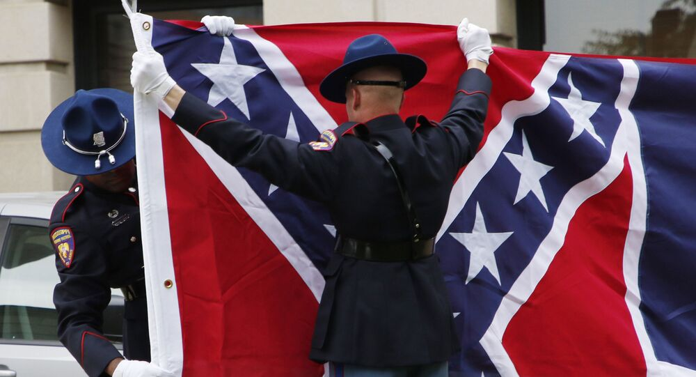 A Mississippi Highway Safety Patrol honor guard folds the retired Mississippi state flag after it was raised over the Capitol grounds one final time in Jackson, Miss., in a July 1, 2020 file photo.