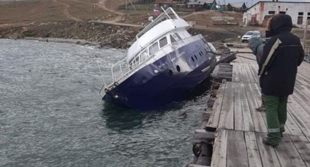 A vessel heeled due to a storm at the pier in the village of Khuzhir