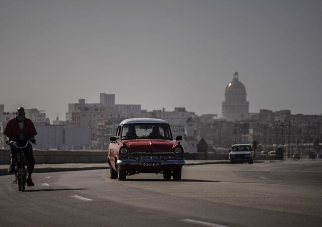 An American classic car and bicycle share the road on the Malecon amid a cloud of Sahara dust in Havana, Cuba, Thursday, June 25, 2020.