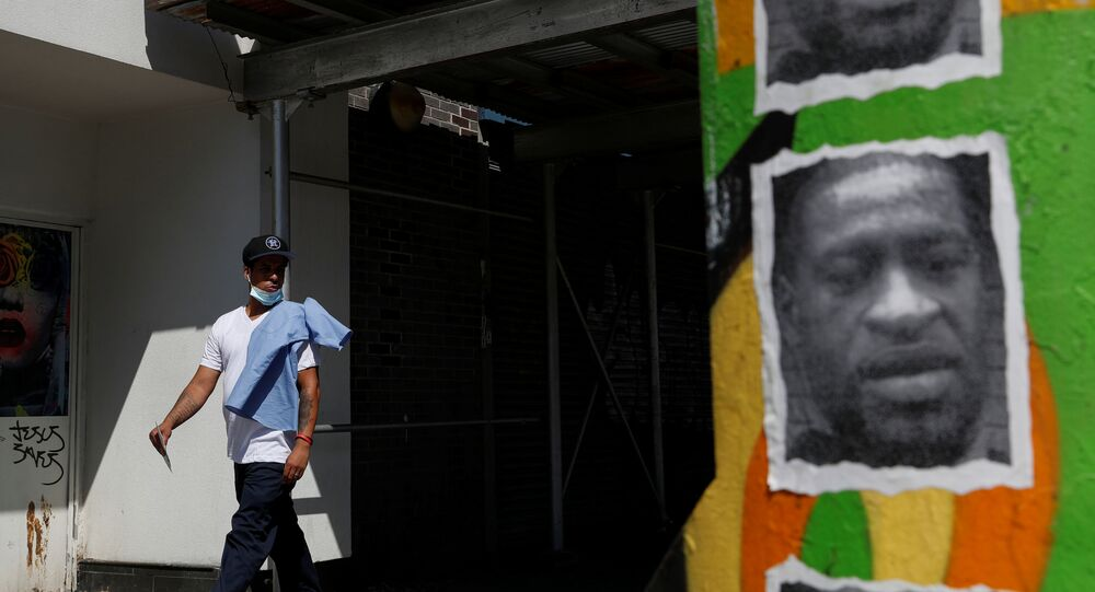 A man walks by a mural of George Floyd, in the aftermath of his death in Minneapolis police custody, along 125th street in the Harlem neighborhood of  New York City, New York, U.S., July 9, 2020.