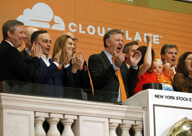 In this Sept. 13, 2019, file photo, Cloudflare co-founder and CEO Matthew Prince, right center, applauds during New York Stock Exchange opening bell ceremonies to celebrate his company's IPO. San Francisco-based Cloudflare said Wednesday, Jan. 15, 2020, it will provide free cybersecurity support to federal election campaigns.