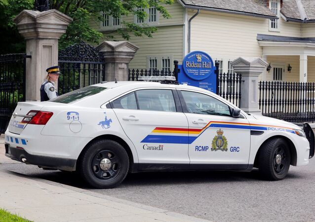 A police officer guards the front gate to Rideau Hall, and the grounds where Canadian Prime Minister Justin Trudeau lives, after an armed man was apprehended on the property early this morning in Ottawa, Ontario, Canada July 2, 2020.